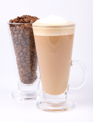 Glass of caffe latte with a glass of coffee beans on white
