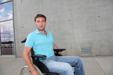 Young man using wheelchair in town