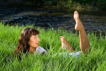 Wondering girl liying in fresh green grass