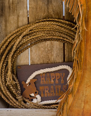 Happy Trails sign, rope and chaps on old wood shelf