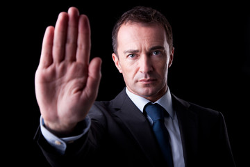 Businessman with his hand raised in signal to stop