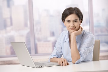 Mid adult woman smiling with computer