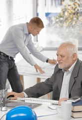 Businessman working with colleague in background
