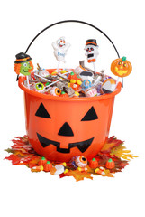 child halloween pumpkin bucket with candy and fall leaves