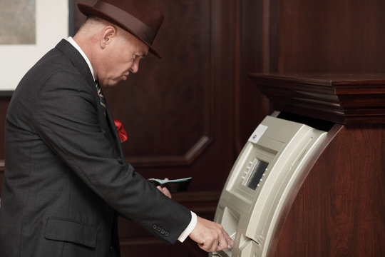 Businessman getting money from the ATM machine