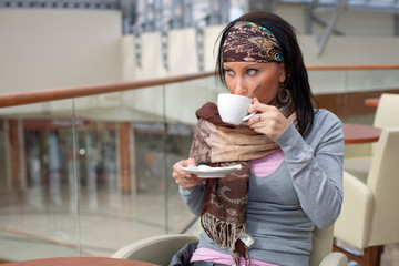 Beautiful young girl is drinking coffee