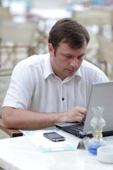 Serious man types on laptop