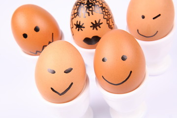 Eggs with smiling faces on white background