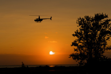 Silhouette of a helicopter from the light of a sunrise.