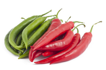 Many red and green chili peppers on white