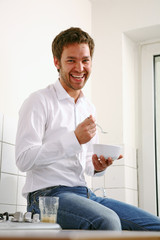 junger mann sitzt in der küche und isst