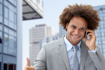 Businessman on the phone in front of modern building