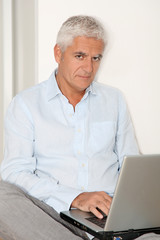 Senior man with laptop sitting on the floor