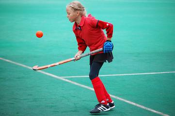Field hockey girl tossing ball up