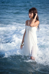 Sexy girl standing in the ocean waves