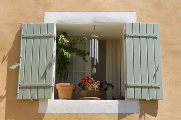 Window with flowerpots and colored shutters. Provence. France.