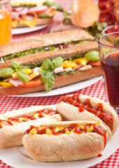 group of hot dogs, sandwiches  and drinks