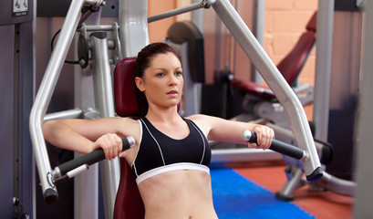 Beautiful athletic woman using a bench press