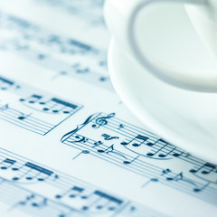 Musical notes and a white coffee cup