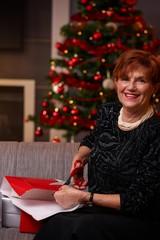 Senior woman wrapping presents at christmas