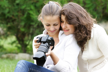 two girl looking through pictures on digital camera