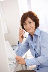 Portrait of senior office worker sitting at desk