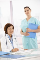 Portrait of senior medical doctor with assistant