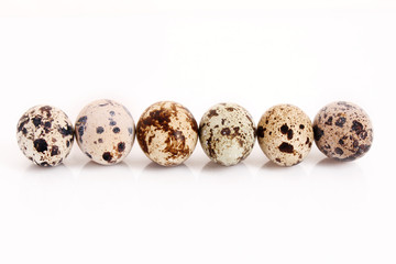 Six different quail eggs in the raw isolated on white