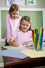 School girls writing in notebook in classroom