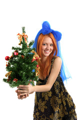 The young beautiful girl in a dress holds a Christmas tree on is