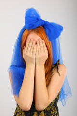 Young woman covering her eyes on grey background