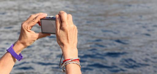 mani tengono macchina fotografica compatta