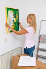 Frau hängt Bild bei Umzug in neue Wohnung auf