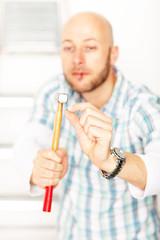 Heimwerker schlägt ein Nagel in die Wand