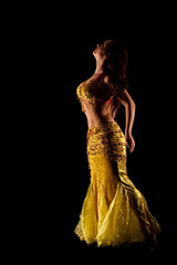 oriental Bellydancer in golden costume, low-key