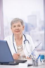 Senior doctor working at desk