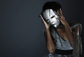 gloomy woman in silver mask posing on a black background.