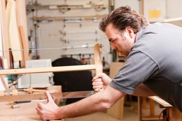 Tischler beim Sägen mit Handsäge
