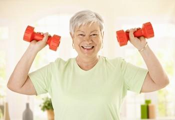 Energetic senior woman with dumbbels
