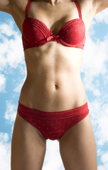 sexy woman body in red lingerie over sky