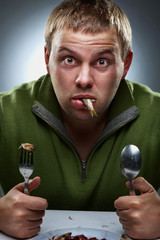 Portrait of hungry man with fish in mouth