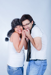 A pregnant couple in winter hat and scarf. In the studio