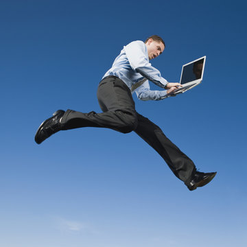 African businessman typing on laptop in mid-air