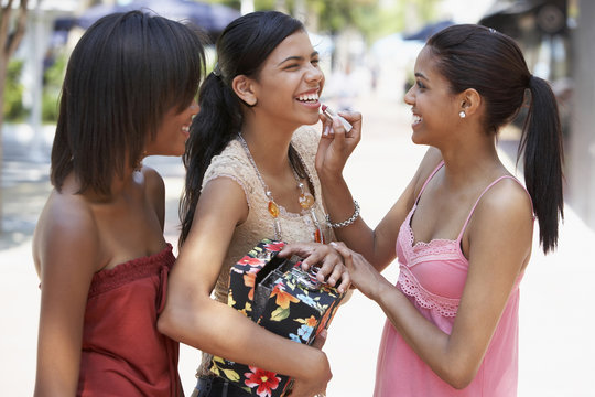 Teenager applying lipstick to friend