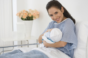 Hispanic mother holding newborn baby in hospital bed