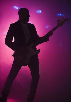 African American man playing guitar at nightclub