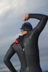 Hispanic woman zipping wetsuit on beach