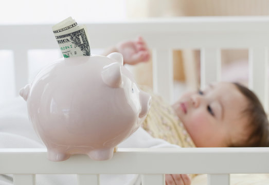 Mixed race baby girl laying in crib next to piggy bank