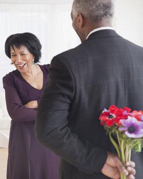 African man bringing wife flowers