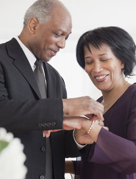 African man attaching bracelet for wife